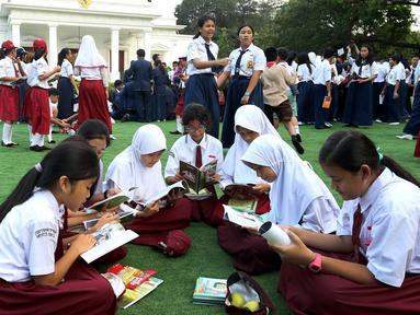 Sejumlah murid sekolah dasar tengah membaca buku di halaman Istana, Jakarta, Rabu (17/8). Sebanyak 500 pelajar menikmati membaca dan mendengarkan dongeng di halaman istana untuk memperingati Hari Buku Nasional. (Liputan6.com/Angga Yuniar)