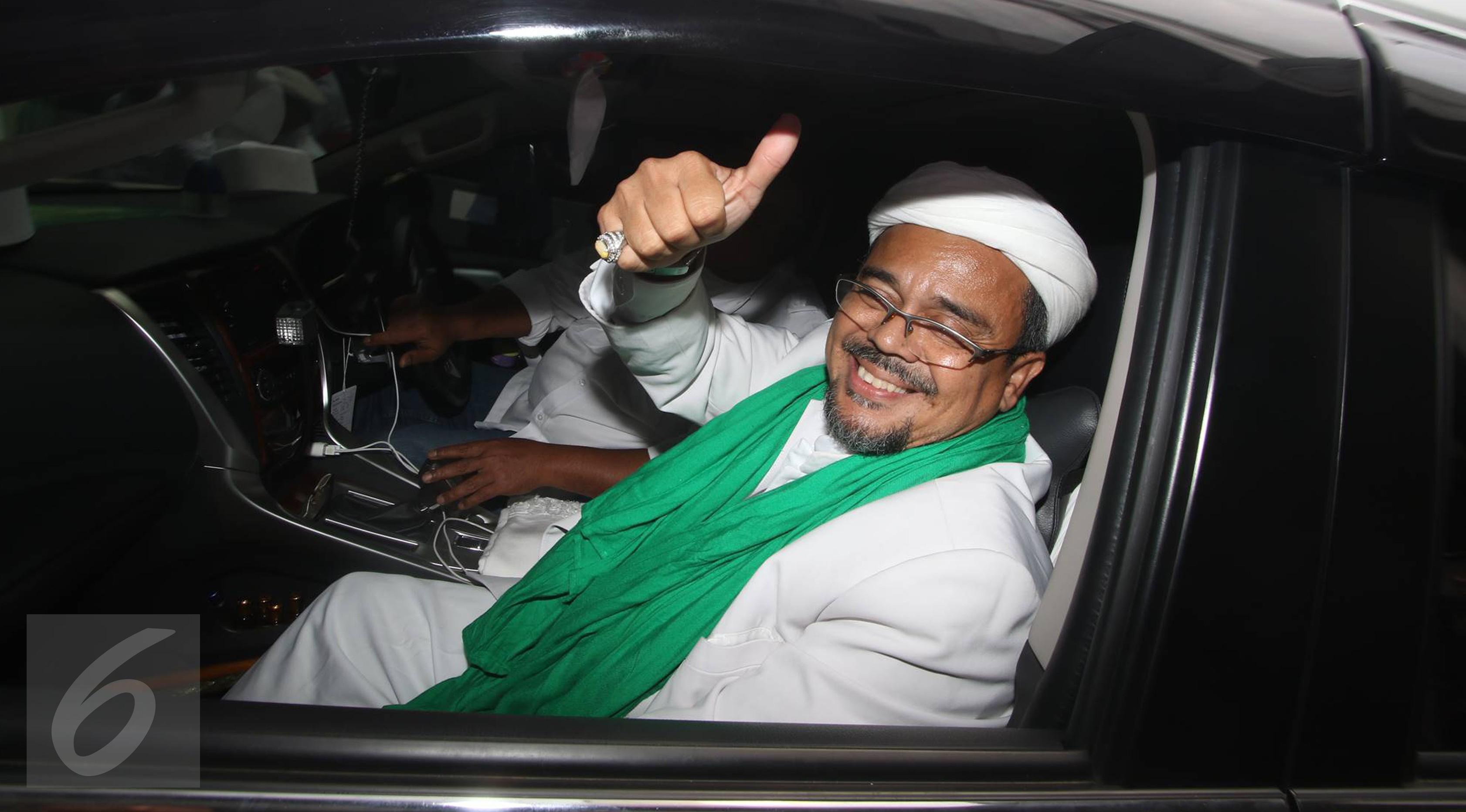Pimpinan FPI, Muhammad Rizieq Shihab menyapa awak media usai menjalani pemeriksaan di Bareskrim, Jakarta, Rabu (23/11). Rizieq diperiksa sebagai saksi ahli dalam kasus penistaan agama yang diduga dilakukan Ahok. (Liputan6.com/Immanuel Antonius)