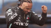 Pembalap Mercedes Lewis Hamilton dari Inggris berselebrasi setelah memenangkan Grand Prix Formula Satu Turki di arena pacuan kuda Istanbul Park di Istanbul, Minggu (15/11/2020). (Tolga Bozoglu/Pool via AP)