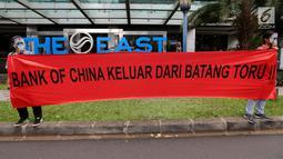 Aktivis WALHI bertopeng orangutan membentangkan spanduk tuntutan saat menggelar aksi di depan Gedung Bank of China, Jakarta, Jumat (1/3). Aksi ini digelar karena izin lingkungan PLTA Batang Toru dianggap cacat. (Liputan6.com/Fery Pradolo)
