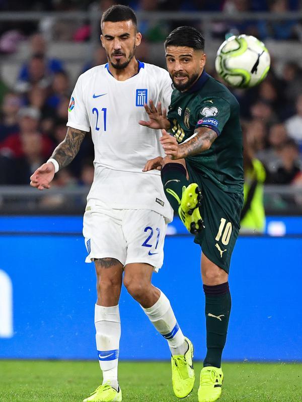 Pemain timnas Yunani Dimitrios Kourbelis berebut bola dengan penyerang timnas Italia, Lorenzo Insigne pada pertandingan grup J babak kualifikasi Piala Eropa 2020 di Stadio Olimpico, Sabtu (12/10/2019). Italia lolos ke putaran final setelah mengalahkan Yunani, 2-0. (Alberto PIZZOLI / AFP)