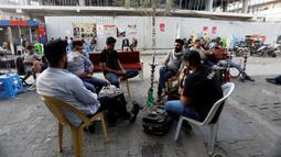Para pria merokok shisha di sebuah kafe di Baghdad, Irak, 9 April 2019.  (REUTERS/Khalid al-Mousily)