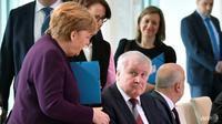 Angela Merkel mengulurkan tangan untuk menyambut Horst Seehofer pada sebuah pertemuan tentang migrasi di Berlin. (AFP / John MACDOUGALL)