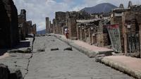 Seorang perempuan mengunjungi situs arkeologi Pompeii seusai kebijakan lockdown selama dua bulan untuk mengendalikan penyebaran Covid-19 di Italia, Selasa (26/5/2020). Salah satu situs arkeologi paling terkenal di dunia ini dibuka kembali untuk umum pada 26 Mei. (AP Photo/Alessandra Tarantino)