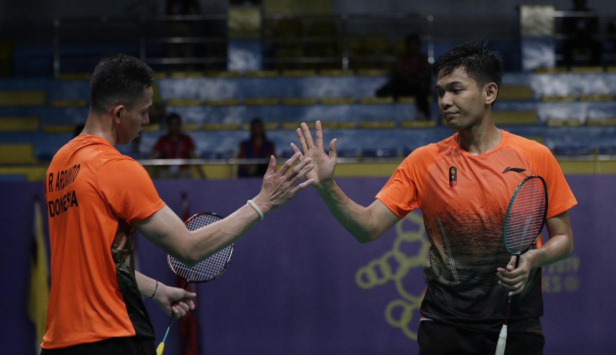 Ganda putra Indonesia, Fajar Rian / Muhammad Rian, melakukan tos saat melawan Aaron Chia / Soh Wooi Yik pada final beregu SEA Games 2019 di Multinlupa Sport Center, Rabu (4/12). Fajar / Rian kalah 17-21 dan 13-21. (Bola.com/M Iqbal Ichsan)