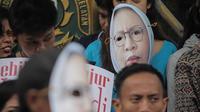 Massa Gerbang (Gerakan Anak Bangsa) mengenakan topeng bergambar  Ratna Sarumpaet  saat unjuk rasa di depan PN Jakarta Selatan, Selasa (19/3). Mereka meminta Ratna Sarumpaet membongkar aktor intelektual dalam penyebaran hoaks. (Liputan6.com/Faizal Fanani)