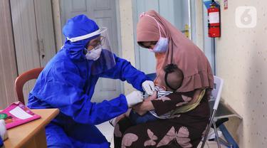 FOTO: Berikan Imunisasi, Bidan di Tangerang Kenakan APD Lengkap