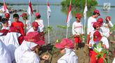 Siswa-siswi  SD Nasima Semarang menanam pohon mangrove di Teluk Pantai Mangunharjo, Mangkang, Tugu, Jumat (18/1). Sebanyak 2500 bibit mangrove ditanam untuk melindungi pantai dan tebing sungai dari proses erosi atau abrasi. (Liputan6.com/Gholib)