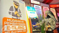 Seorang wanita membayar denda tilang dengan sistem tilang elektronik atau e-tilang melalui mesin ATM BRI di Jakarta, Jumat (16/12). e-Tilang adalah sistem aplikasi pembayaran denda tilang melalui sistem e-banking atau ATM. (Liputan6.com/Angga Yuniar)