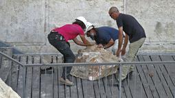 Pekerja Otoritas Pengurus Benda Antik Israel berusaha memindahkan batu besar yang jatuh dari Tembok Ratapan di Kota Tua Yerusalem, Rabu (25/7). Insiden ini terjadi di area yang tergolong tidak terlalu banyak dikunjungi peziarah Yahudi (AFP/AHMAD GHARABLI)