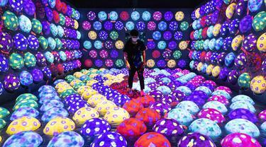 "Seorang anggota staf berjalan melalui instalasi digital interaktif bernama ""Rapidly Rotating Bouncing Sphere Caterpillar House"" selama pratinjau media ""teamLab Forest"" di gedung hiburan BOSS E・ZO FUKUOKA di Fukuoka, Jepang, Jumat (16/7/2021). (YUKI IWAMURA/AFP)"