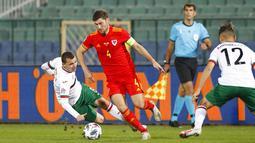 Pemain Wales, Ben Davies, berusaha melewati pemain Bulgaria pada laga UEFA Nations League di Stadion Vassil Levski, Kamis (15/10/2020). Wales menang dengan skor 1-0. (AP Photo/Anton Uzunov)