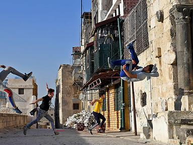 Pemuda Suriah berlatih parkour di Aleppo, Suriah utara, (7/4). Setelah pemerintah Suriah mengambil alih kendali penuh Aleppo dari pasukan pemberontak Desember 2016, beberapa pemuda kini menyalurkan hobinya, yaitu parkour.  (AFP Photo/George Ourfalian)
