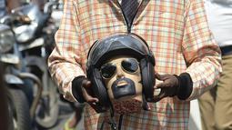 Seorang sukarelawan berpakaian seperti pengendara sepeda motor memegang kepala mockup dengan helm mengambil bagian dalam kampanye kesadaran keselamatan jalan dengan petugas polisi di Chennai (7/7/2021). (AFP/Arun Sankar)