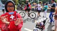 Relawan menunjukkan mini kit P3K yang akan dibagikan kepada pengguna CFD di Jalan MH Thamrin, Jakarta, Minggu (25/9). Kegiatan ini mengajak masyarakat untuk selalu siap dengan P3K. (Liputan6.com/Fery Pradolo)