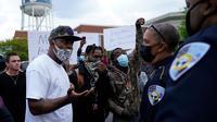 Orang-orang berbicara dengan polisi selama protes di Elizabeth City, NC, setelah seorang deputi menembak mati seorang pria kulit hitam pada Rabu (21/4/2021). (AP/ Gary Broome)