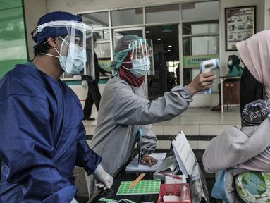 Petugas paramedis memeriksa suhu tubuh seorang ibu sebelum mengantarkan anaknya mengikuti imunisasi di Puskesmas Kecamatan Jatinegara, Jakarta, Kamis (26/11/2020). (merdeka.com/Iqbal S. Nugroho)