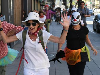 Para peserta berdandan seperti badut mengejar pejalan kaki selama 'Running of the Clowns' di Pasadena, California pada 21 Oktober 2018. Lari dikejar kawanan badut ini merupakan parodi yang mengolok-olok lomba dikejar banteng di Spanyol. (Mark RALSTON/AFP)