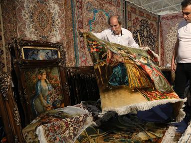 Pedagang memamerkan karpet tenun dagangannya kepada pengunjung pameran di Teheran, Iran, Kamis (29/8/2019). Eksportir karpet Iran kehilangan pasar AS setelah Presiden Donald Trump menjatuhkan sanksi berat terhadap negara tersebut. (AP Photo/Vahid Salemi)