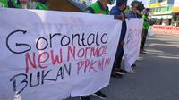 Menolak penerapan PPKM, sejumlah Pengemudi Ojek Online (Ojol) menggelar aksi damai di Bundaran Hulondalo Indah (HI), Kota Gorontalo. (Arfandi Ibrahim/Liputan6.com)