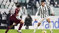 Bintang Juventus Cristiano Ronaldo mencoba melewati pemain Torino Romas Rincon pada pekan ke-10 Liga Italia di Allianz Stadium, Minggu (6/12/2020) dini hari WIB. (Marco Alpozzi/LaPresse via AP)