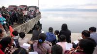 Keluarga dan warga berdoa untuk penumpang yang hilang dari kecelakaan KM Sinar Bangun di Danau Toba di Pelabuhan Tigaras, Sumatra Utara, Indonesia (21/6). KM Sinar Bangun tenggelam pada Senin (18/6) sore. (AP Photo/Binsar Bakkara)