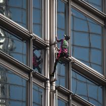 Alain Robert yang dijuluki 'French Spiderman' memanjat gedung pencakar langit Cheung Kong Center di Hong Kong, Jumat (16/8/2019). Pria berusia 57 tahun tersebut memanjat Cheung Kong Center dalam kondisi panas dan lembab pada Jumat pagi. (Lillian SUWANRUMPHA/AFP)