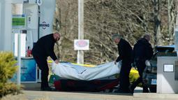Petugas medis mengevakuasi korban penembakan di sebuah pom bensin di Enfield, Nova Scotia, Minggu (19/4/2020). Aksi itu ia lancarkan dalam kurun waktu selama 12 jam, lapor pihak berwenang. (Tim Krochak/The Canadian Press via AP)
