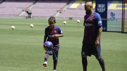 Pemain baru Barcelona, Arturo Vidal, bersama anaknya Alonso, saat perkenalan di Stadion Camp Nou, Senin, (7/8/2018). Barcelona merogoh kocek sebesar 19 juta euro untuk mengamankan jasa pria berkebangsaan Cile itu. (AFP/Josep Lago)
