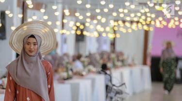 Model membawakan busana karya desainer Intan Kusuma dan Atina Maulia di Akuatik GBK Senayan, Jakarta, Kamis (2/5/2019). Sebanyak 30 koleksi busana hijab dengan nama Vanilla Raya diperagakan menyambut bulan suci Ramadan. (Liputan6.com/Fery Pradolo)