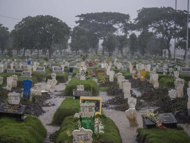 "Keluarga memasang hiasan dari besi bertuliskan ""My Love"" di sebuah pusara di lahan khusus korban Covid-19 di TPU Keputih, Surabaya, Jawa Timur, Kamis (7/1/2020). Kasus penyebaran Covid-19 di Surabaya masih tinggi.  (AFP/Juni Kriswanto)"