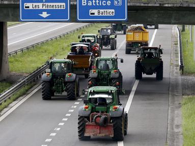 Peternak sapi perah menaiki traktor mereka di jalan tol atau jalan bebas hambatan saat melakukan aksi protes di Battice, Belgia, Kamis (30/7/2015). Aksi protes tersebut berkaitan dengan rendahnya harga jual susu. (REUTERS/Francois Lenoir)