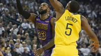 Bintang LA Lakers, LeBron James (kiri) diadang pemain Golden State Warriors, Kevon Looney dalam laga lanjutan NBA 2018-2019 (Foto: AP Photo/Tony Avelar)