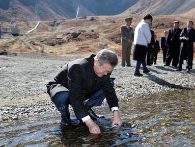Presiden Korea Selatan Moon Jae-in memasukkan air kawah ke dalam botol di Gunung Paektu, Korea Utara, Kamis (20/9). Gunung Paektu merupakan gunung berapi yang dianggap sakral di Korea Utara. (Pyongyang Press Corps Pool via AP)