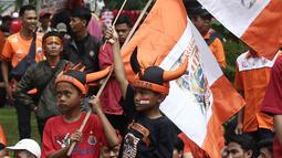 Jakmania mengibarkan bendera Persija saat penyerahan piala Liga I di depan Balai Kota, Jakarta, Sabtu (15/12). Kemenangan Persija di Liga 1 jadi momen bersejarah bagi masyarakat Ibu Kota. (Liputan6.com/Herman Zakharia)