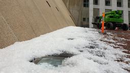 Es sebesar bola golf berserakan di luar Gedung Parlemen setelah hujan es dan badai di Canberra, Senin (20/1/2020). Badai petir dan hujan es melanda sebagian pesisir timur Australia bersamaan saat sejumlah wilayah yang dilanda kekeringan di Australia dilanda badai debu (HO/Courtesy of Don Arthur/AFP)