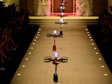 Deretan pesawat tanpa awak (drone) membawa koleksi tas tangan Dolce & Gabbana pada Milan Fashion Week 2018, Minggu (25/). Drone ini keluar dari belakang panggung, lalu terbang sambil membawa koleksi tas yang harganya terbilang selangit (Miguel MEDINA/AFP)