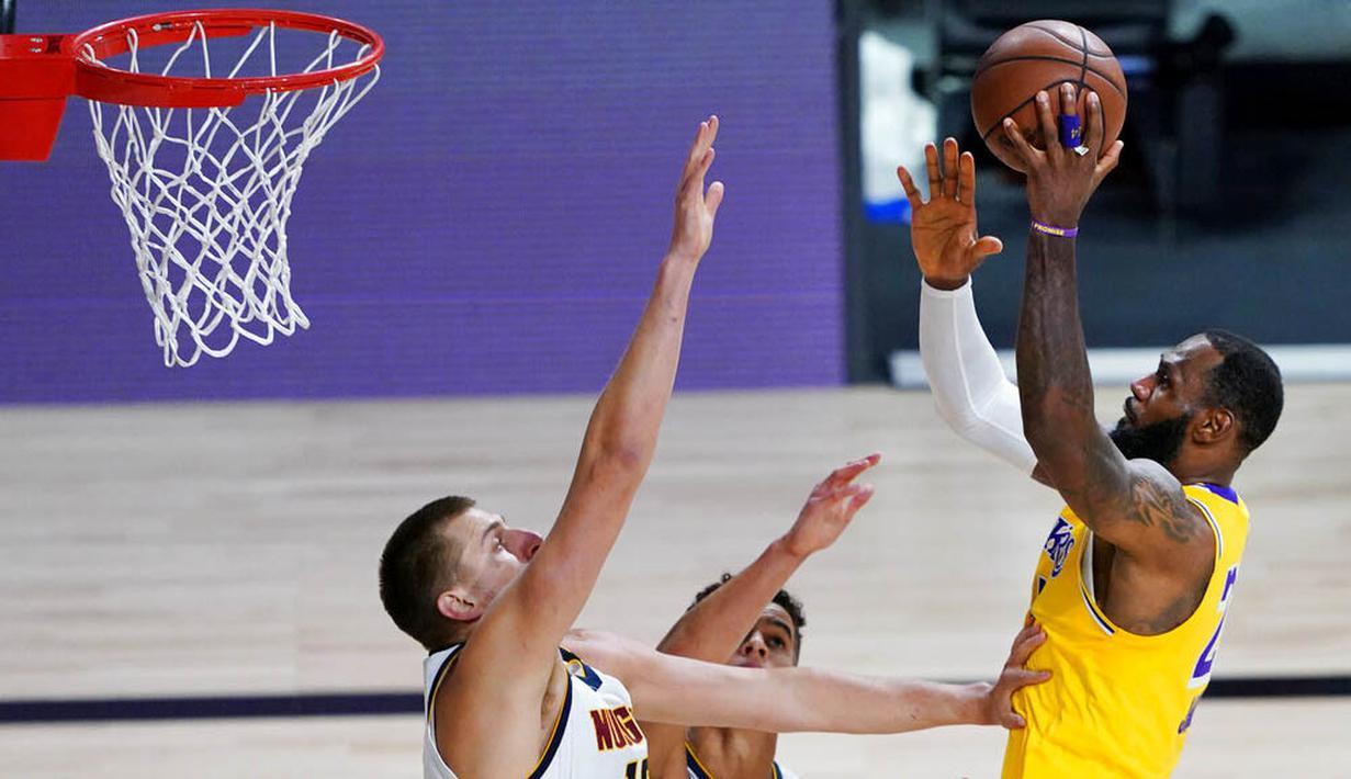 Pebasket Los Angeles Lakers, LeBron James, berusaha memasukkan bola saat melawan Denver Nuggets pada laga NBA di The Arena, Senin (11/8/2020). LA Lakers menang dengan skor 124-121. (AP Photo/Ashley Landis, Pool)