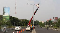 Aktivitas pekerja ketika memasang lampu light emitting diode (LED) di Jakarta, Selasa (26/7). Secara bertahap, Pemprov DKI akan menggunakan lampu LED yang hemat energi untuk Penerangan Jalan Umum (PJU) di seluruh Jakarta. (Liputan6.com/Immanuel Antonius)