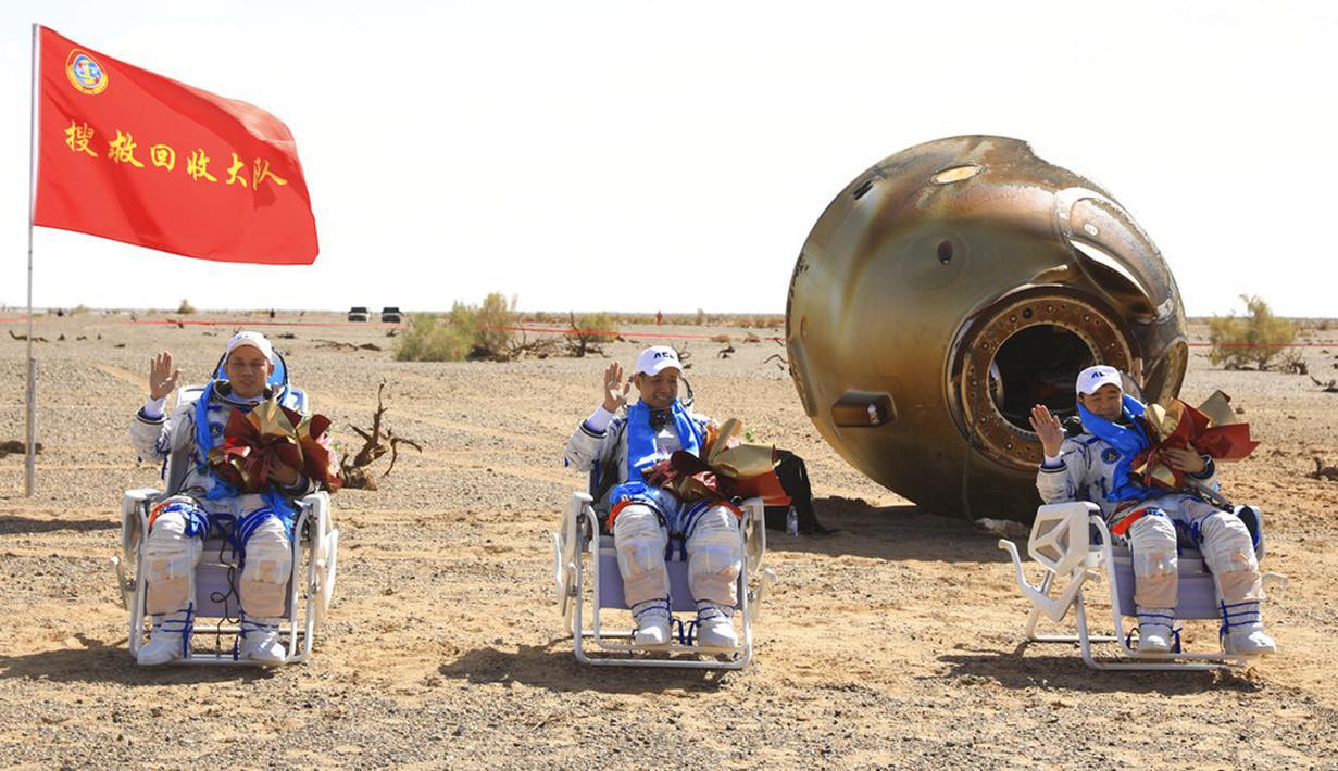 Astronot China Tang Hongbo (kiri), Nie Haisheng (tengah), dan Liu Boming (kanan) melambai di lokasi pendaratan Dongfeng di Daerah Otonomi Mongolia Dalam, China, 17 September 2021. Trio astronot China kembali ke Bumi setelah misi luar angkasa. (Ju Zhenhua/Xinhua via AP)