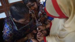 Seorang anak menangis saat diberikan vaksin polio selama kampanye vaksinasi polio di Karachi, Pakistan (9/4). Pakistan adalah salah satu dari hanya dua negara di dunia di mana polio, penyakit masa kecil yang melumpuhkan. (AFP Photo/Rizwan Tabassum)