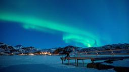 Seorang wanita duduk di dermaga untuk menonton Aurora Borealis atau Northern Lights di di Kepulauan Lofoten, Bostad, lingkaran Arktik, Norwegia, Sabtu (3/3). Cahaya Aurora biasa terlihat di sekitar daerah Kutub Utara dan Selatan. (Olivier MORIN/AFP)