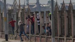 Para pemuda Kashmir berlindung saat bentrok dengan tentara paramiliter India di Srinagar, Kashmir, India, (1/4). Pengunjuk rasa memprotes menyusul tewasnya delapan pemberontak dalam bentrokan dengan pasukan pemerintah. (AP Photo / Dar Yasin)