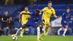 Penyerang  Chelsea, Tammy Abraham, berusaha melewati pemain Barnsley, Cauley Woodrow, pada laga Piala Liga Inggris di Stadion Stamford Bridge, Kamis (24/9/2020). Chelsea menang dengan skor 6-0. (AP Photo/Neil Hall)