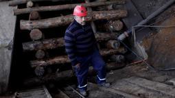 Seorang penambang batubara berdiri didepan pintu akses yang diblokir selama protes menuntut pemerintah untuk menyediakan dana untuk membuka kembali tambang batubara Santa Ana, di kota Curanilahue, Chile, (26/12). (Reuters/Juan Gonzalez Galaz)