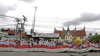 Bendera Merah-Putih sepanjang 50m dibentangkan anak-anak sekolah saat balapan Tour de Singkarak 20116 pada etape ke-7 di daerah Dharmasraya, Sumatera Barat, (12/8/2016). (Bola.com/Nicklas Hanoatubun)