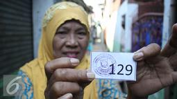 Seorang warga memperliharkan kupon pengambilan sembako, Jakarta, Kamis (3/9/2015). Presiden Jokowi bersama Gubernur Ahok mengadakan blusukan dan membagikan semabko pada warga di kawasan Cilincing. (Liputan6.com/Gempur M Surya)