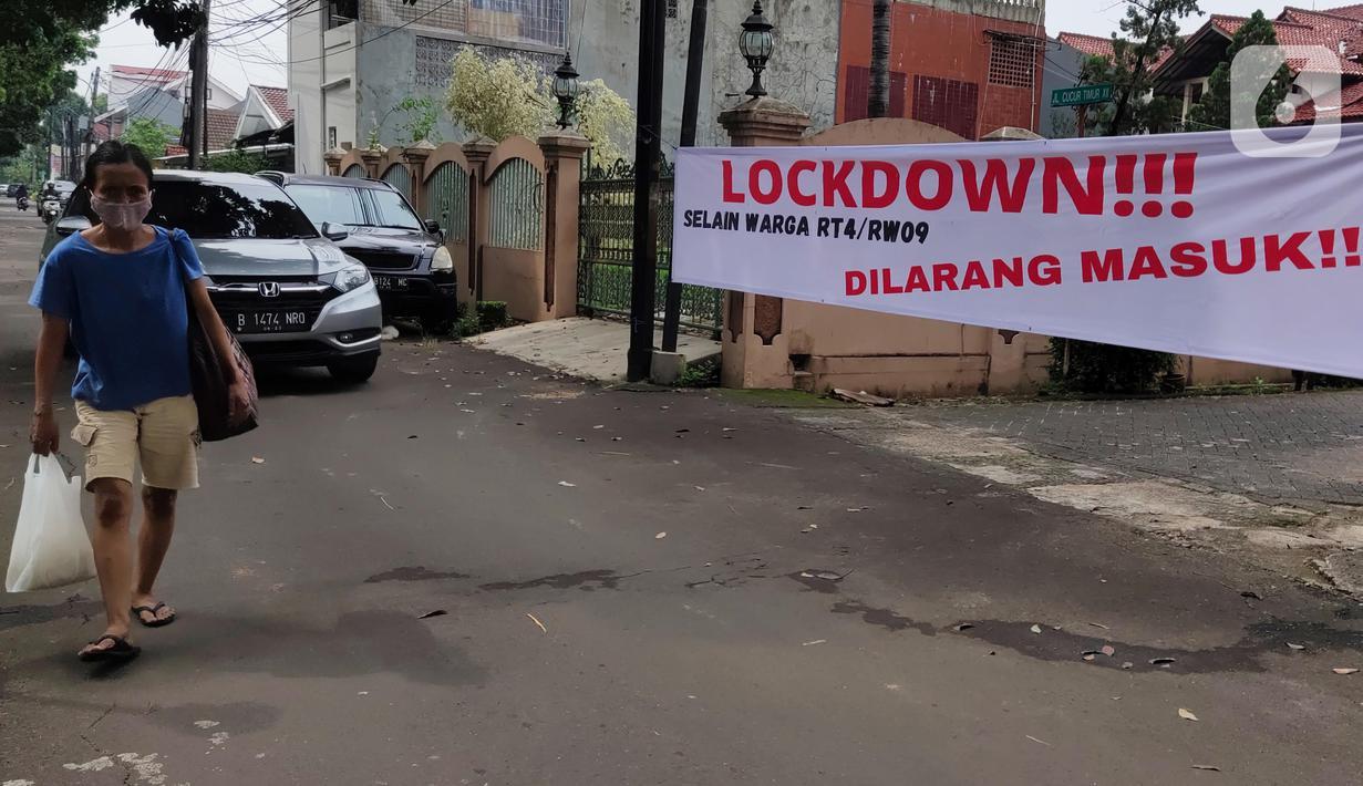Pejalan kaki melintas di depan spanduk pemberitahuan lockdown di RT 04 / RW 09 Kelurahan Pondok Karya, Tangerang Selatan, Rabu (23/6). Melonjaknya kasus covid-19 di beberapa kawasan membuat sejumlah wilayah melakukan karantina di tingkat RT untuk memutus penyebaran corona (Liputan6.com/Angga Yuniar)