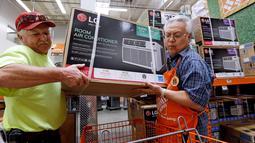 Manager toko mengambilkan pendingin udara untuk pelanggan menjelang gelombang panas di toko perlengkapan Home Depot di Seattle, Selasa (1/8). Suhu panas mendekati 100 derajat diperkirakan terjadi di wilayah itu pada Kamis 3 Agustus. (AP/Elaine Thompson)