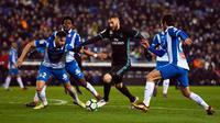 Pemain Real Madrid, Karim Benzema berebut bola dengan pemain Espanyol Marc Granero dan Granero pada pertandingan pekan ke-26 La Liga, di Stadion RCDE, Selasa (27/2). Real Madrid harus menyerah dari Espanyol dengan skor akhir 0-1. (Josep LAGO / AFP)